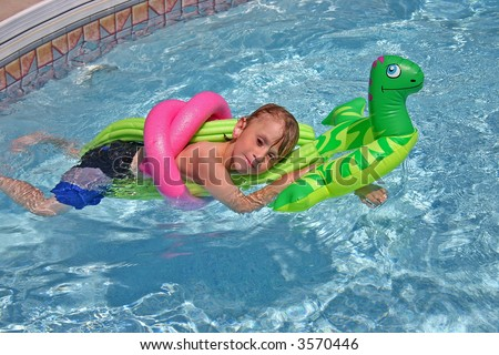 Boy Relaxing In a Pool with a peaceful look on his face - stock photo