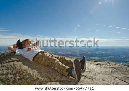 Boy Relaxing on Cliff - stock photo
