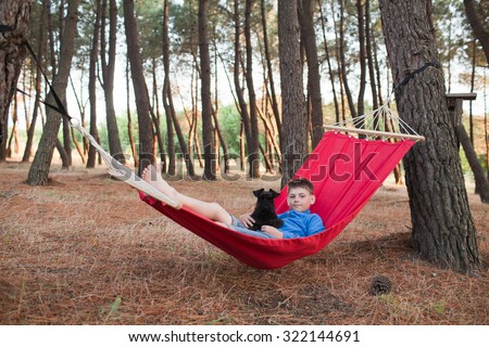 Boy relaxing with family dog in a hammock in pine forest - stock photo