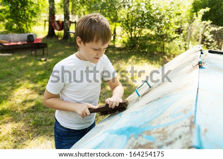 Boy removes paint from the box on the back yard. Preparation for painting.