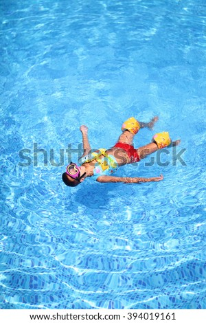 Boy resting in a pool in the diving mask and Personal flotation device
