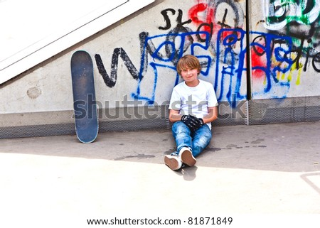 boy resting with skate board at the skate park - stock photo