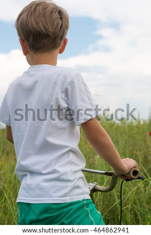 Boy riding a bike outdoors in the grass on a sunny day