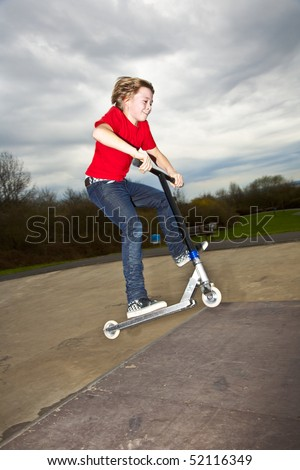 Boy riding a scooter going airborne at a scooter park