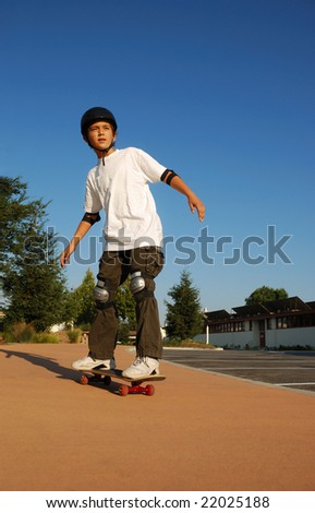 Boy riding a skateboard in afternoon sun