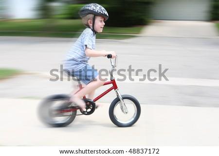 Boy riding bike (motion blur) - stock photo