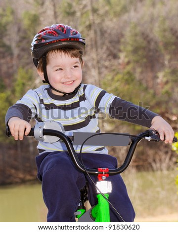 Boy riding bike with safety helmet outdoors at park