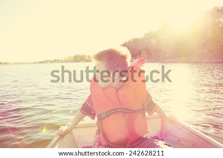 Boy riding in a  boat on a lake. Instagram effect. - stock photo
