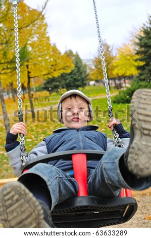 Boy riding on a swing in autumn park - stock photo