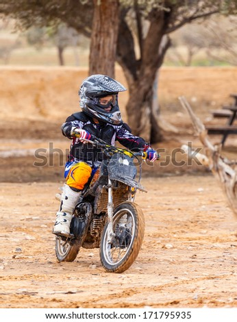 boy riding on motorcycle, dirt - stock photo