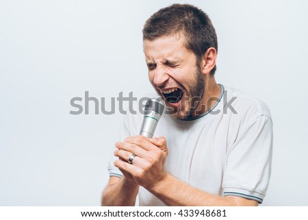 Boy Rocking Out. Image of a handsome man singing to the microphone. Emotional portrait of an attractive guy - stock photo