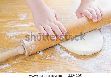 Boy rolls out the dough