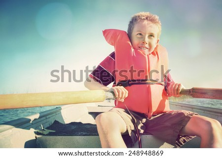 Boy rowing a boat on a lake.  Instagram effect