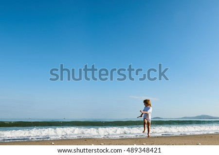 boy running away from the waves