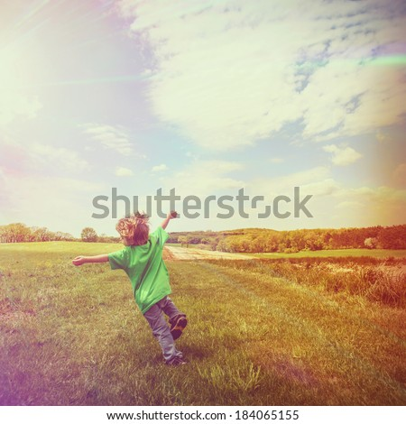 Boy running in a grassy field - stock photo