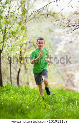 Boy running in a park or garden among trees - stock photo