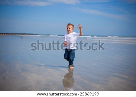 Boy running on a beach, wearing jeans - stock photo