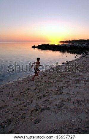 Boy running on beach toward setting sun. - stock photo