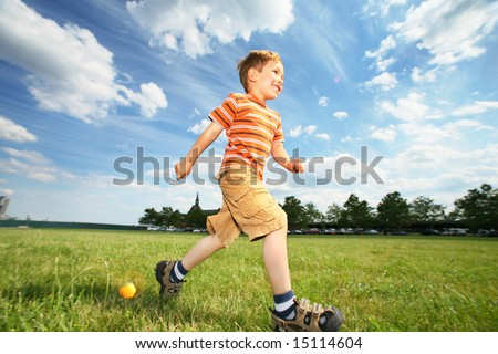 Boy running on green grass field under beautiful blue sky with scenic white  clouds. - stock photo