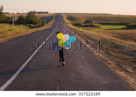 Boy runs on road with balloons