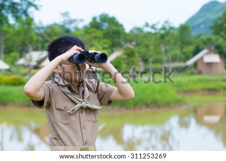 Boy Scout, a Thai Asian young boy scout in uniform exploring with binocular in the forest - stock photo