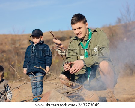 Boy Scout in Uniform Cooking Sausages on Stick next to Smoking Campfire While Young Boy Looks On - stock photo