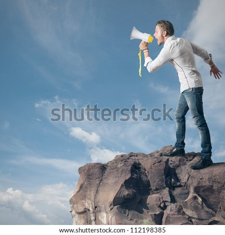 Boy screaming on the megaphone in the mountain - stock photo