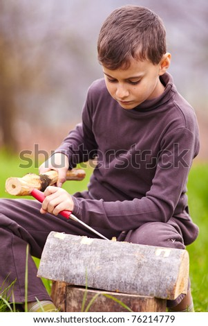 Boy sculpting with a chisel into the bark of a beech log outdoor - stock photo