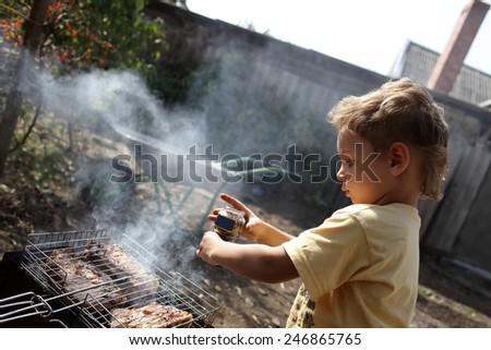 Boy seasoning pork chops with pepper at the backyard - stock photo