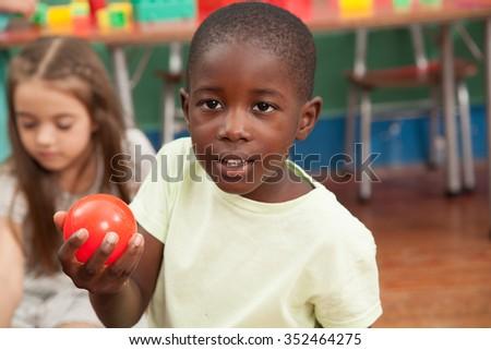 Boy sharing a plastic ball - stock photo