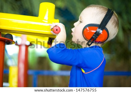 Boy shooting from a toy gun - stock photo