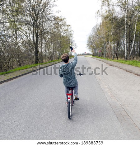 boy shoots a picture with his mobile while riding bike - stock photo