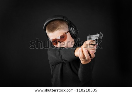 boy shoots from a gun with glasses and headphones