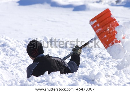 Boy shoveling deep snow - stock photo