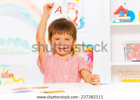 Boy showing letter flashcard in reading class - stock photo