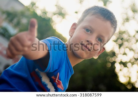 Boy Showing Thumb Up Sign, Photo Against Sun, Focus On Face - stock photo