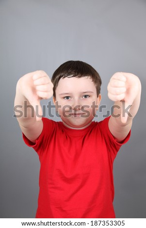 Boy showing thumbs down on a gray background - stock photo