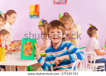 Boy shows his crafted with paper in class