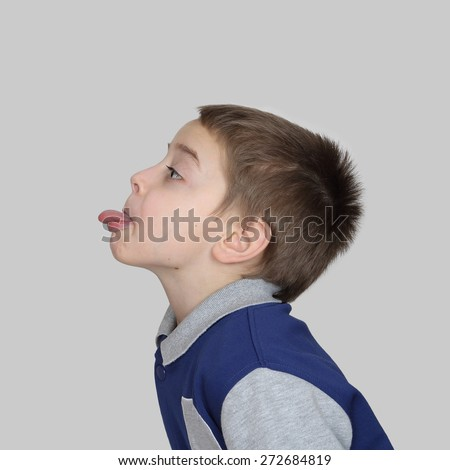Boy shows his tongue side view in square on gray background - stock photo