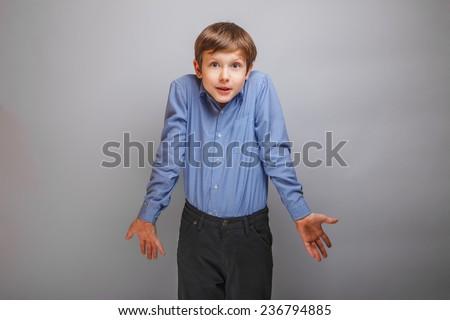 boy shrugs from ignorance surprised - stock photo