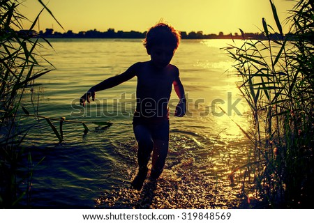 Boy silhouette running out of water on the beach at sunset. - stock photo