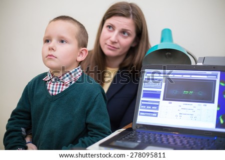 boy sits in mothers lap at a reception at the ophthalmologist - stock photo