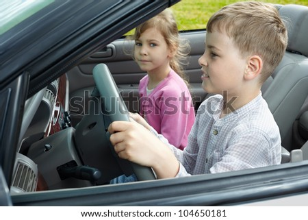 Boy sits on a driver seat in open top car and his sister sits on passenger seat, focus on boy, close-up. - stock photo