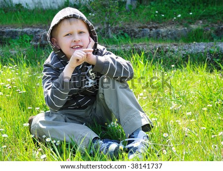 boy sits on the camomile forest meadow and points right - stock photo