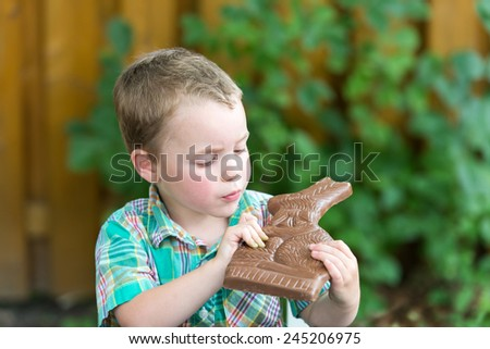 Boy sits outside looking at a chocolate bunny he is holding in his hands on Easter day during the spring season.  There is a bite out of the chocolate bunny.  Room for copy space.  Part of a series. - stock photo