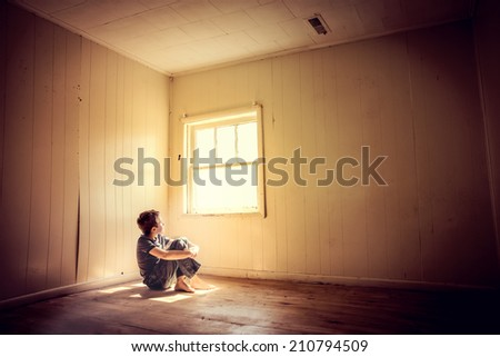 Boy sitting alone looking out the window with rays of lighting s - stock photo