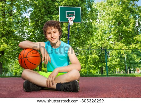 Boy sitting alone with elbow on the ball - stock photo