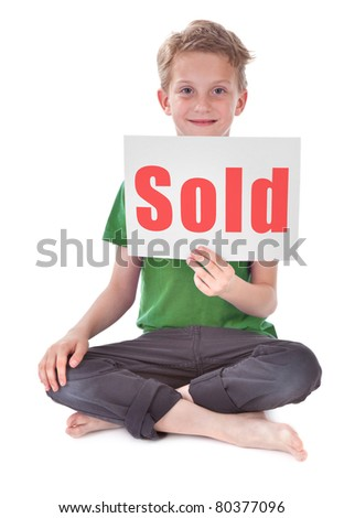 boy sitting and holding white page with sold inscription - stock photo