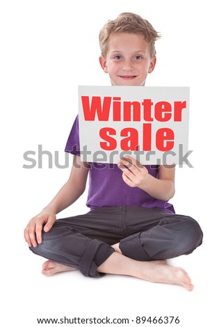 boy sitting and holding white page with winter sale word - stock photo