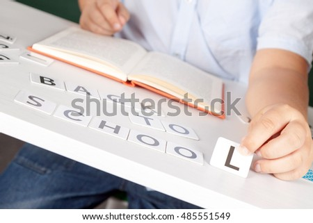boy sitting at school desk with the inscription of the numbers back to school